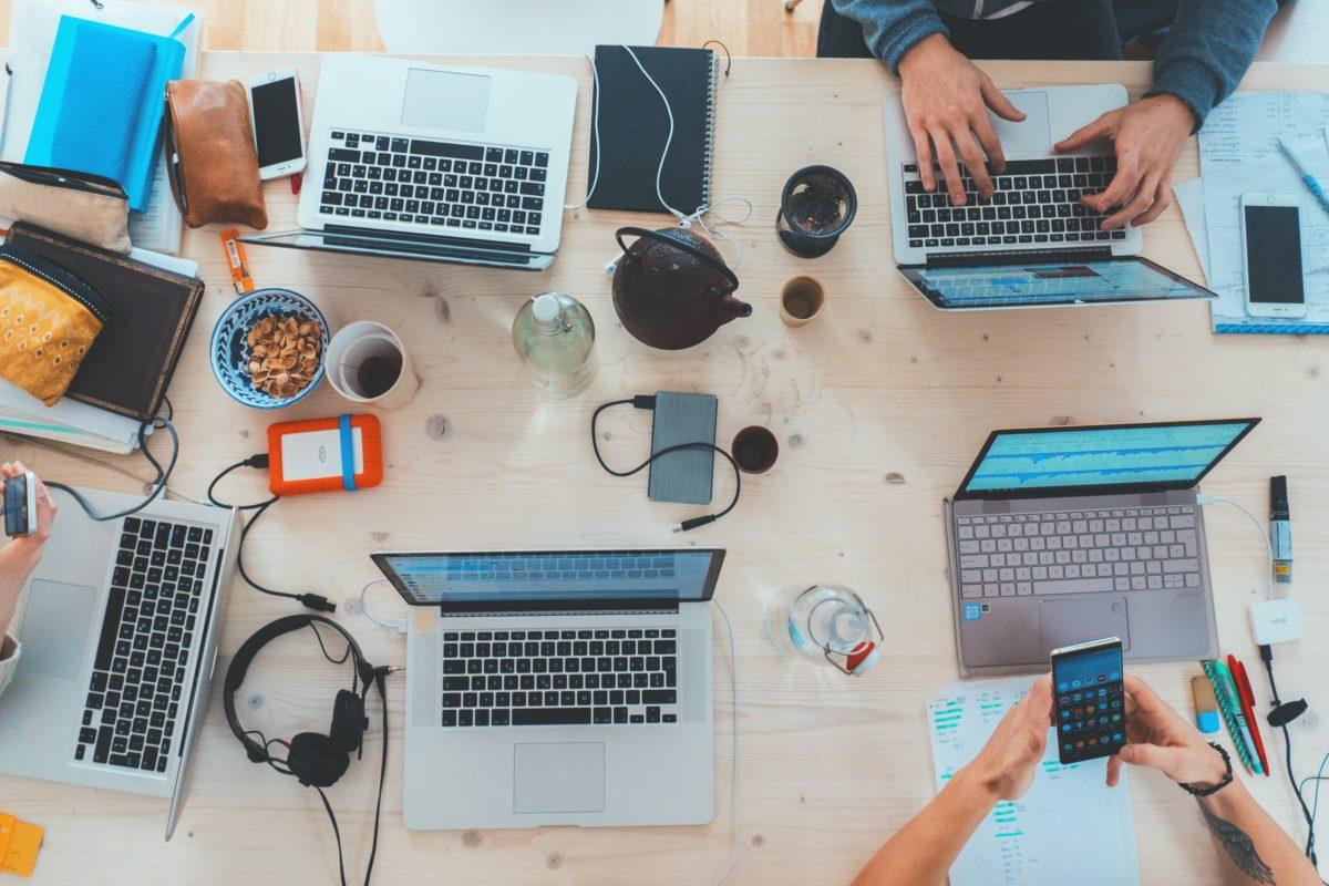 עמדת עבודה במשרד יחסי ציבור עם חמישה מחשבים ניידים על שולחן עבודה משותף