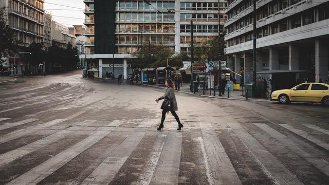 אישה חוצה כביש ברחוב שהעסקים בו סגורים